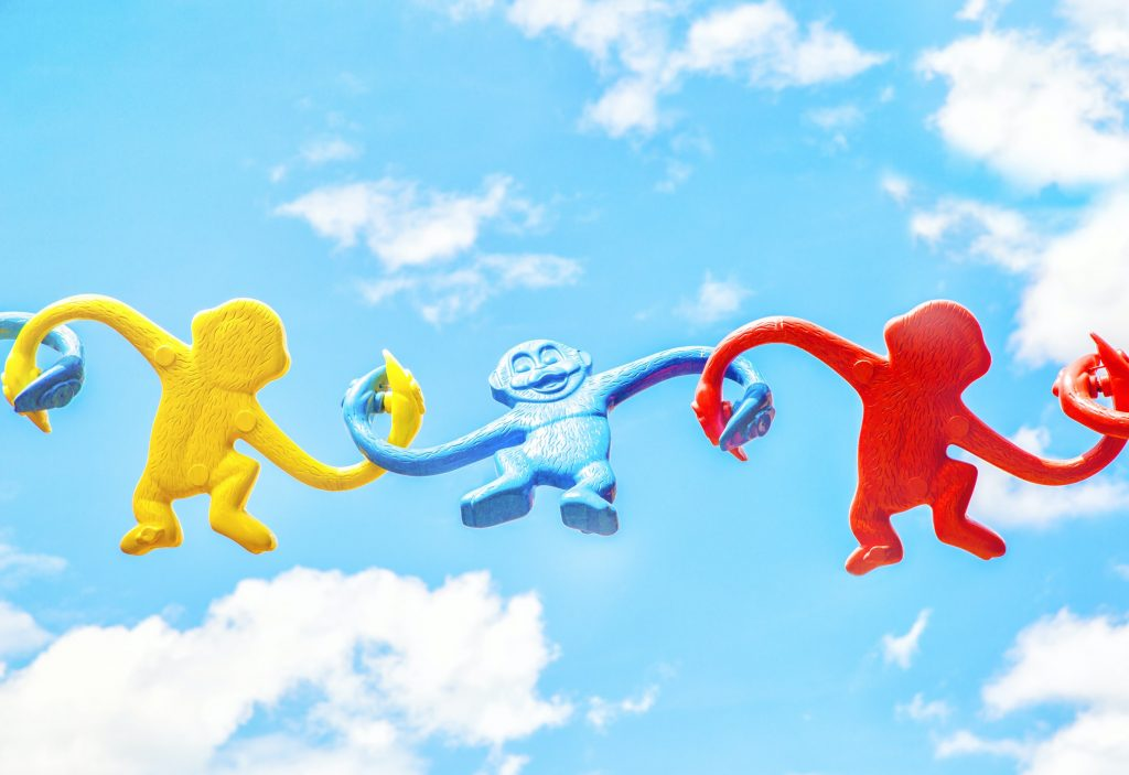 A photo image of plastic toy monkeys linking arms