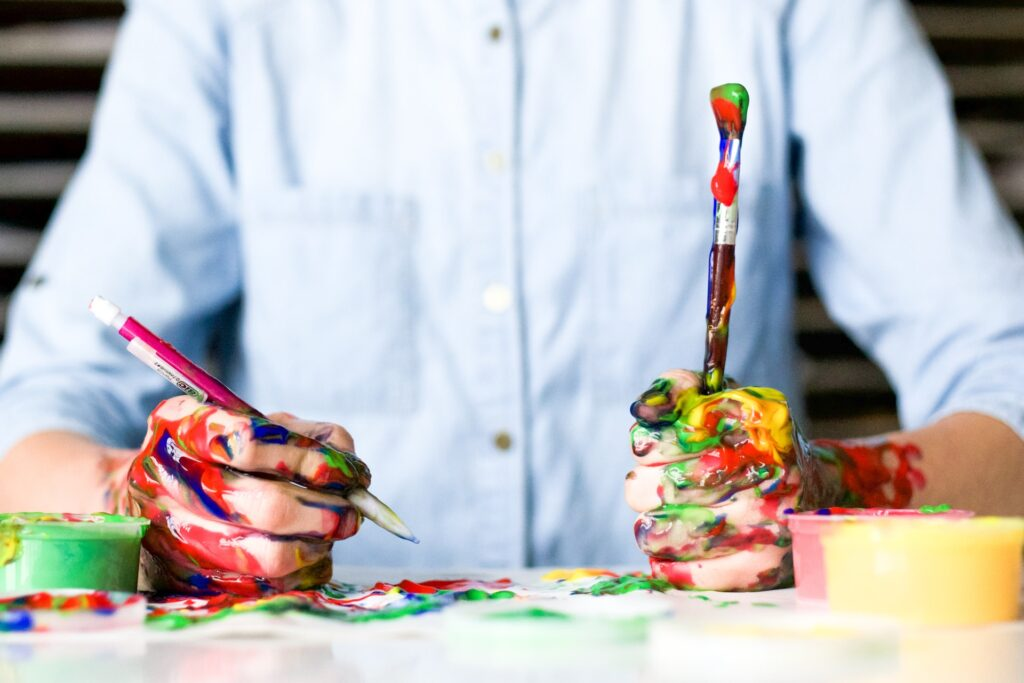 Mid torso of a person hold paint brushes with hands covered in paint