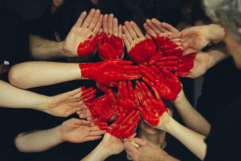Image of a red heart painted onto a number of hands
